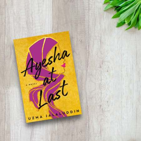 ayesha at last book cover against timber background